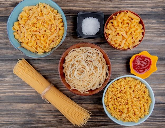 Bovenaanzicht van verschillende macaronis als spaghetti rotini vermicelli en anderen met zout en ketchup op hout Gratis Foto