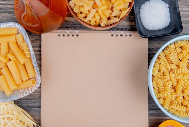 Bovenaanzicht van verschillende macaronis als ziti rotini tagliatelle en anderen met gesmolten boterzout rond notitieblok op hout met kopie ruimte Gratis Foto