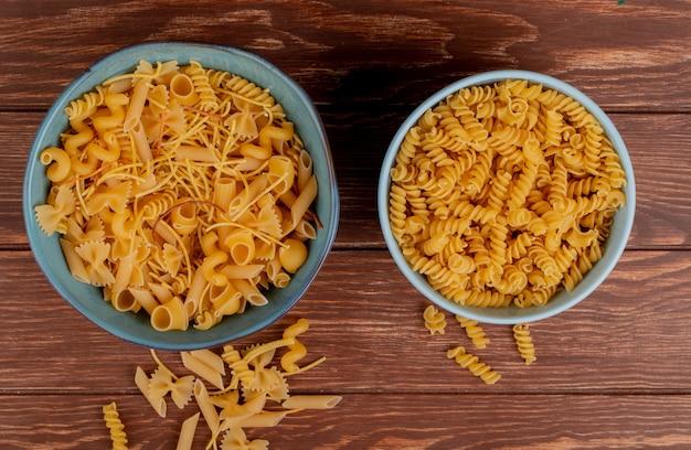 Bovenaanzicht van verschillende macaronis en rotini macaronis in kommen en op hout Gratis Foto