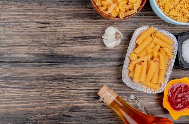 Bovenaanzicht van verschillende macaronis zoals ziti rotini en anderen met knoflook gesmolten boterzout en ketchup op hout met kopie ruimte Gratis Foto
