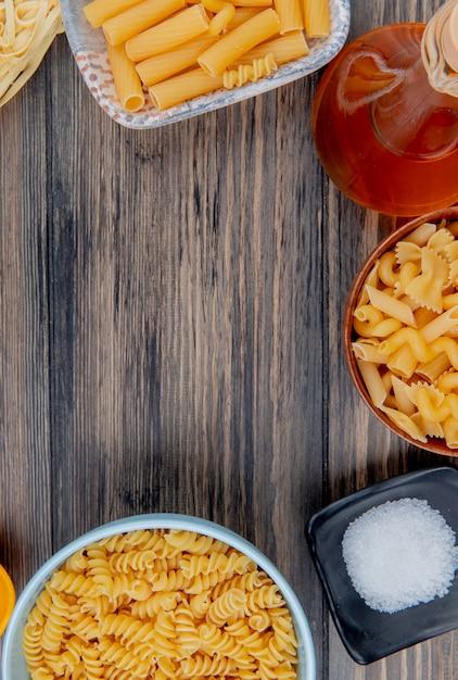 Bovenaanzicht van verschillende macaronis zoals ziti rotini tagliatelle en anderen met gesmolten boterzout op hout met kopie ruimte Gratis Foto