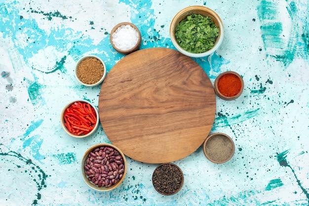 Bovenaanzicht van verschillende seizoensborden met paprika bonen en greens op lichtblauw bureau, peper ingrediënt pittig heet voedsel Gratis Foto