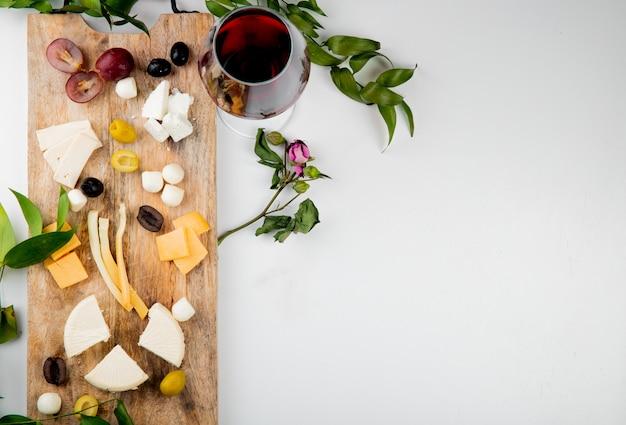 Bovenaanzicht van verschillende soorten kaas met stukjes druiven olijven op snijplank met rode wijn op wit versierd met bloemen en bladeren met kopie ruimte Gratis Foto