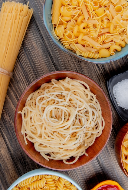 Bovenaanzicht van verschillende soorten pasta als spaghetti rotini vermicelli en anderen met zout en ketchup op houten oppervlak Gratis Foto