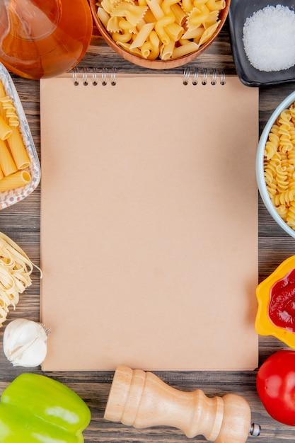 Bovenaanzicht van verschillende soorten pasta als ziti rotini tagliatelle en anderen met knoflook gesmolten boter zout tomatenpeper en ketchup rond notitieblok op houten oppervlak met kopie ruimte Gratis Foto