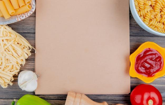 Bovenaanzicht van verschillende soorten pasta als ziti rotini tagliatelle en anderen met knoflook, tomatenpeper en ketchup rond notitieblok op houten oppervlak met kopie ruimte Gratis Foto