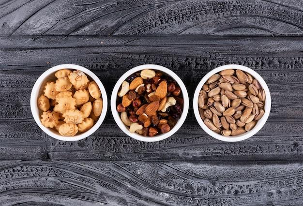 Bovenaanzicht van verschillende soorten snacks als noten en crackers in kommen op donkere horizontaal Gratis Foto
