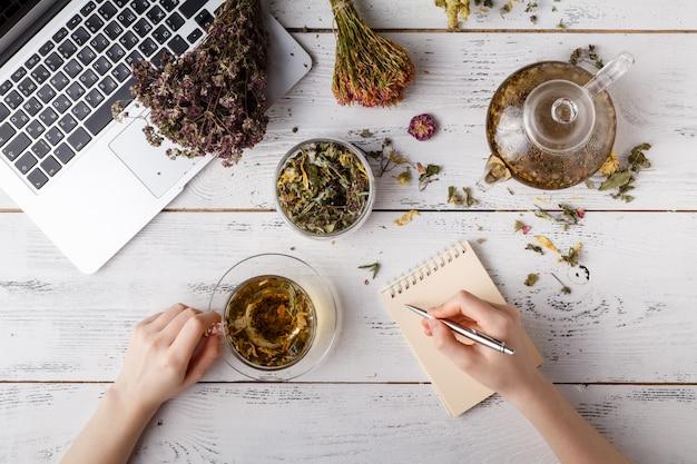 Bovenaanzicht van verschillende soorten thee. op smaak gebracht met diverse kruiden, een appel, roos met een theepot en een theekopje op een rustieke tafel Premium Foto