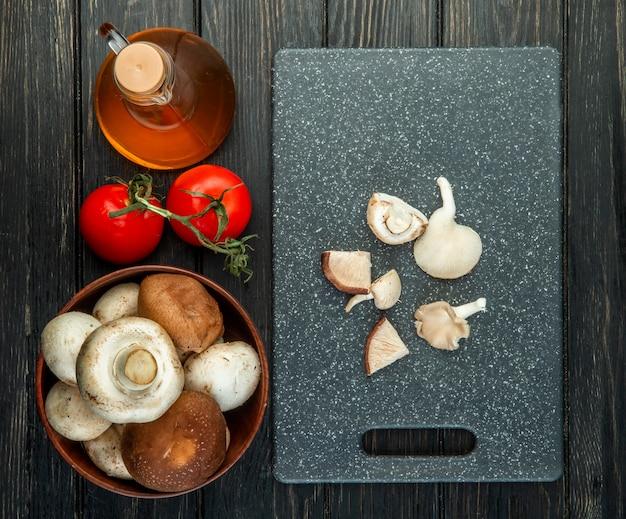 Bovenaanzicht van verse champignons in een houten kom fles olijfolie en verse tomaten gesneden champignons op zwarte snijplank op zwart Gratis Foto