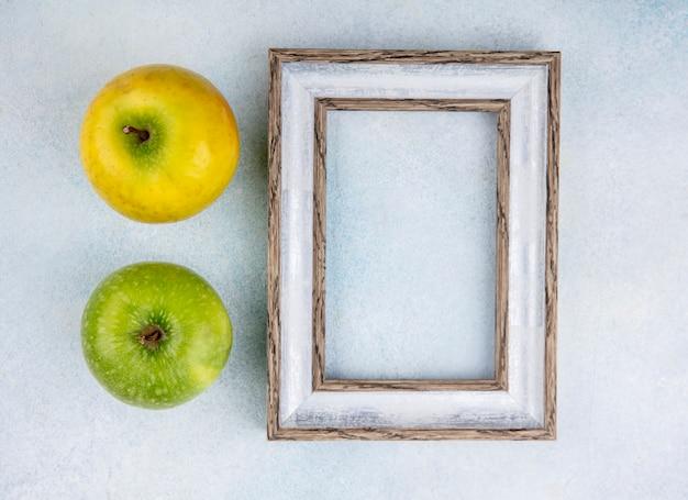 Bovenaanzicht van verse en kleurrijke appels met leeg fotolijstje met op wit Gratis Foto