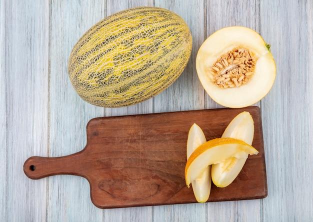 Bovenaanzicht van verse en rijpe plakjes meloen op houten keukenbord met meloenen op grijs hout Gratis Foto