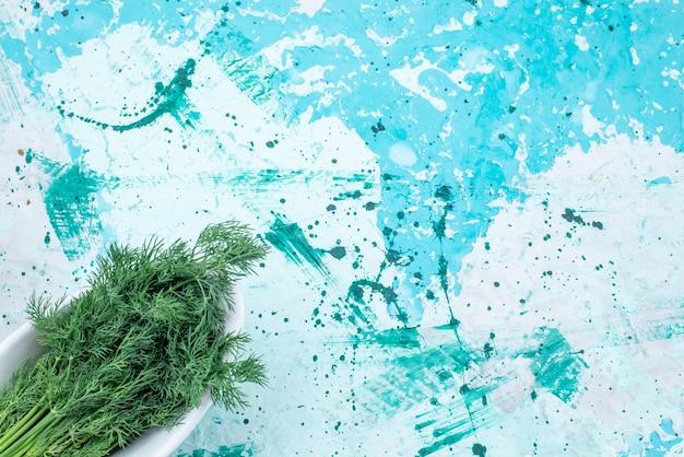 Bovenaanzicht van verse greens geïsoleerd in plaat op helderblauw, groen blad product voedsel maaltijd groente Gratis Foto