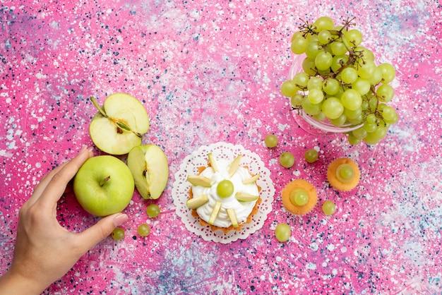 Bovenaanzicht van verse groene druiven geheel zuur en heerlijk fruit met kleine cake op licht, fruit vers zacht sap Gratis Foto