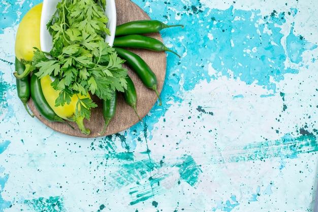 Bovenaanzicht van verse groenten geïsoleerd in plaat samen met groene paprika's en pittige paprika's op helderblauw bureau, groen blad product voedsel maaltijd groente Gratis Foto