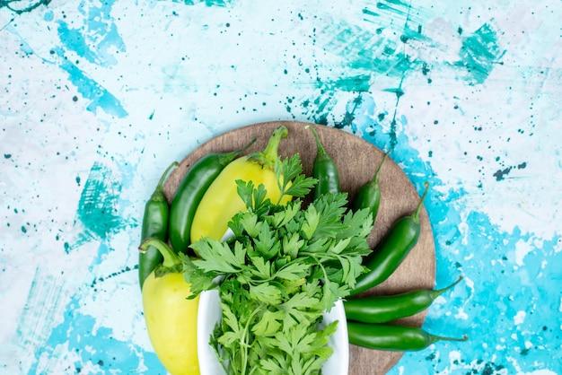 Bovenaanzicht van verse groenten geïsoleerd in plaat samen met groene paprika's en pittige paprika's op helderblauw, groen blad product voedsel maaltijd groente Gratis Foto