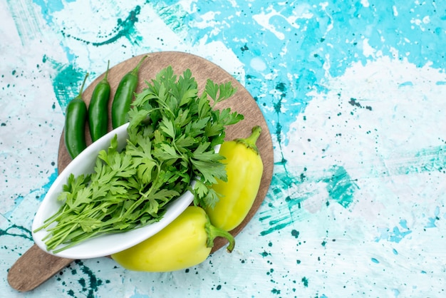 Bovenaanzicht van verse groenten geïsoleerd in plaat samen met groene paprika's en pittige paprika's op helderblauwe, groene bladproduct voedselmaaltijd Gratis Foto