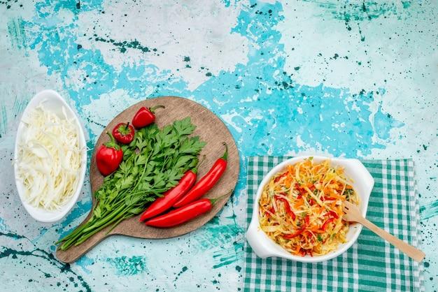 Bovenaanzicht van verse groenten samen met rode pittige paprikasalade kool op helderblauw, plantaardig groen voedselingrediënt Gratis Foto