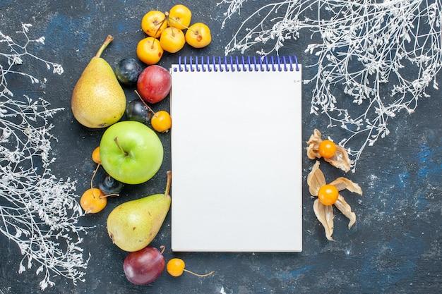 Bovenaanzicht van verse groenten zoals peren groene appel gele kersen pruimen en blocnote op donker bureau, fruit vers bessenvoedsel Gratis Foto