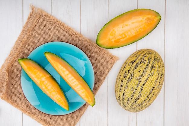 Bovenaanzicht van verse meloenen op blauw bord op zakdoek met plakjes op wit Gratis Foto