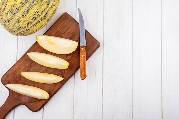 Bovenaanzicht van verse plakjes meloenen op houten keukenbord met mes op wit hout Gratis Foto