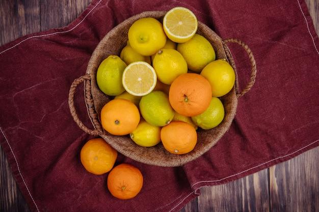 Bovenaanzicht van verse rijpe citroenen en sinaasappelen in een rieten mand op donkerrode stof op rustiek Gratis Foto