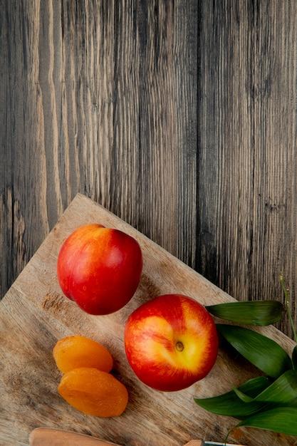 Bovenaanzicht van verse rijpe nectarines met gedroogde abrikozen op houten snijplank op rustieke achtergrond met kopie ruimte Gratis Foto