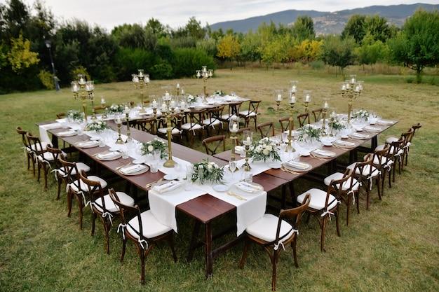 Bovenaanzicht van versierd met minimale bloemenboeketten bruiloft feesttafel met chiavari stoelen buiten in de tuinen met uitzicht op de bergen Gratis Foto