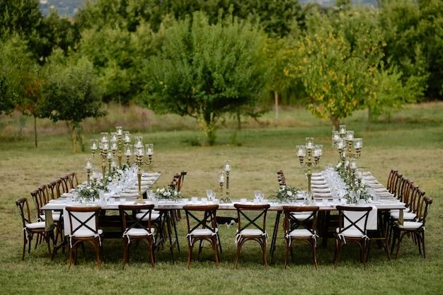 Bovenaanzicht van versierd met minimale bloemenboeketten en kaarsen bruiloft feesttafel met chiavari stoelen buiten in de tuinen voor fruitbomen Gratis Foto