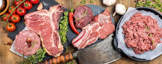 Bovenaanzicht van vlees met hakmes en kruiden Gratis Foto