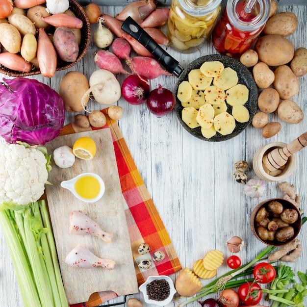 Bovenaanzicht van voedsel en groenten als zure tomaat kippenpoot gebakken aardappel kool bloemkool selderij en anderen op houten achtergrond met kopie ruimte Gratis Foto