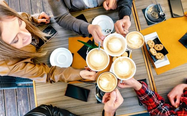Bovenaanzicht van vrienden roosteren cappuccino in coffeeshop restaurant Premium Foto