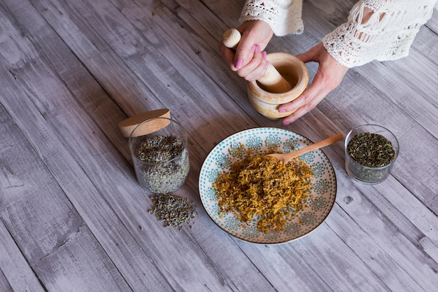 Bovenaanzicht van vrouw handen met ingrediënten op tafel, houten mortel, gele kurkuma, lavendel en groene natuurlijke bladeren. overdag dichten Premium Foto