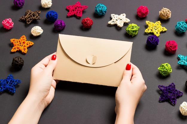 Bovenaanzicht van vrouw met een envelop op zwart gemaakt van vakantie decoraties. Premium Foto