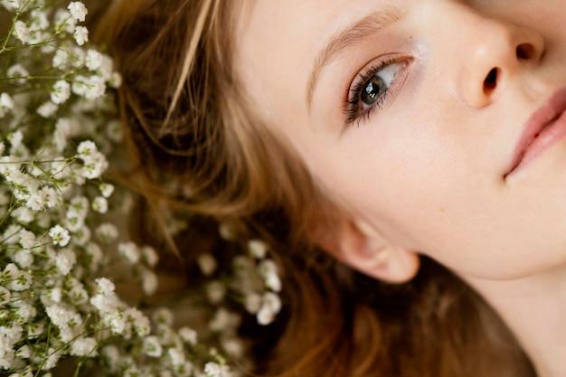 Bovenaanzicht van vrouw poseren met lentebloemen Premium Foto