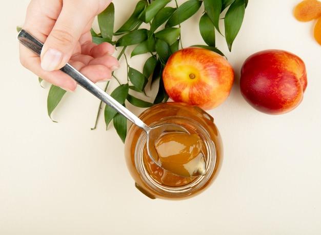 Bovenaanzicht van vrouwelijke hand met een lepel met perzik jam over de glazen pot en verse nectarines met groene bladeren op wit Gratis Foto