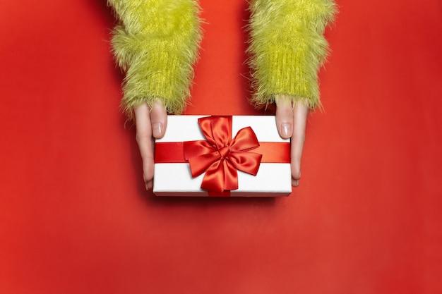 Bovenaanzicht van vrouwelijke handen in groene trui, met een witte geschenkdoos met rood lint op achtergrond van rode kleur. Premium Foto