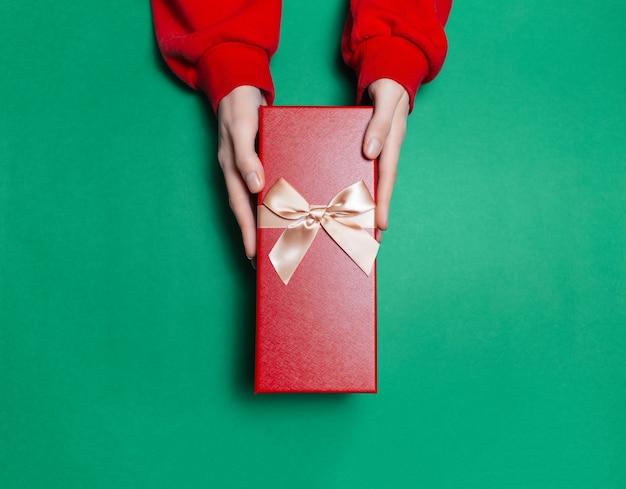 Bovenaanzicht van vrouwelijke handen met geschenkdoos op oppervlak van groene kleur Premium Foto