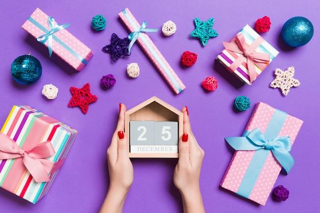 Bovenaanzicht van vrouwelijke handen met kalender op paarse achtergrond Premium Foto