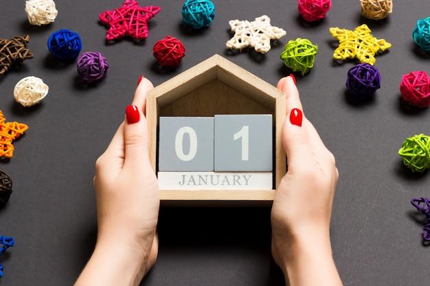 Bovenaanzicht van vrouwelijke handen met kalender op zwarte achtergrond Premium Foto
