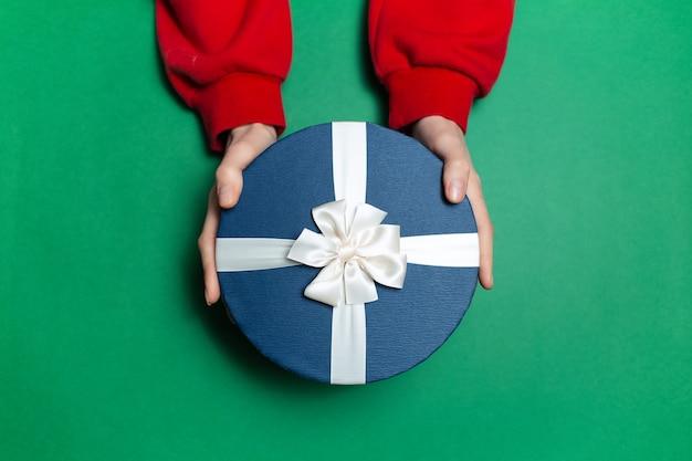 Bovenaanzicht van vrouwelijke handen met ronde blauwe geschenkdoos met witte strik op oppervlakte groene kleur Premium Foto