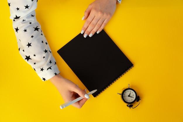 Bovenaanzicht van vrouwelijke handen schrijven in notitieblok Premium Foto