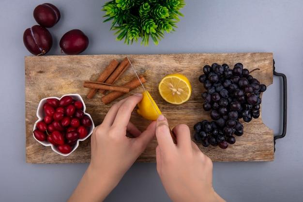 Bovenaanzicht van vrouwelijke handen snijden citroen met mes cornel bessen en druiven kaneel op snijplank en plukken plant op grijze achtergrond Gratis Foto