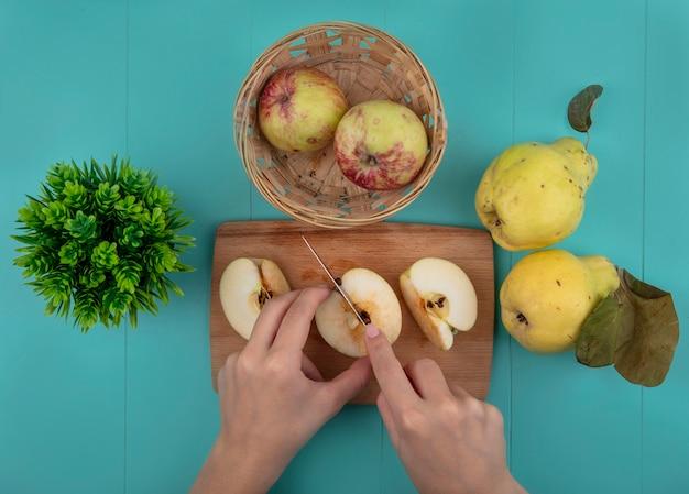 Bovenaanzicht van vrouwelijke handen verse appel snijden op een houten keuken bord met mes op een blauwe achtergrond Gratis Foto