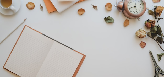 Bovenaanzicht van vrouwelijke vintage werkruimte met open notebook- en kantoorbenodigdheden Premium Foto