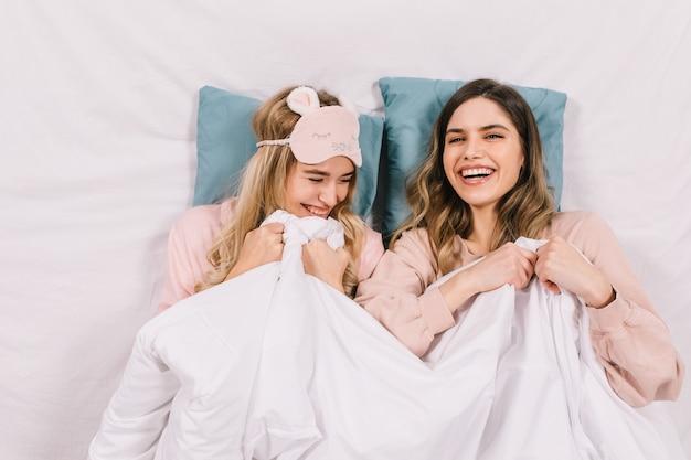 Bovenaanzicht van vrouwen lachen in bed Gratis Foto