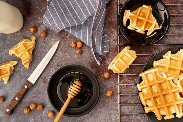 Bovenaanzicht van wafels bedekt met honing met hazelnoten en honingdipper Gratis Foto