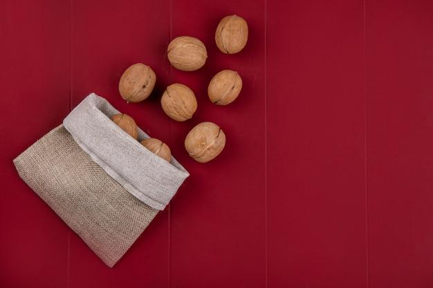 Bovenaanzicht van walnoten in een jutezak op een rode ondergrond Gratis Foto