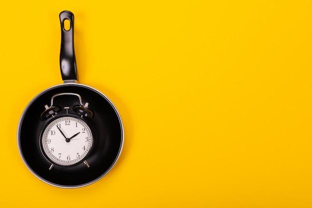 Bovenaanzicht van wekker in geïsoleerde pan geel Premium Foto