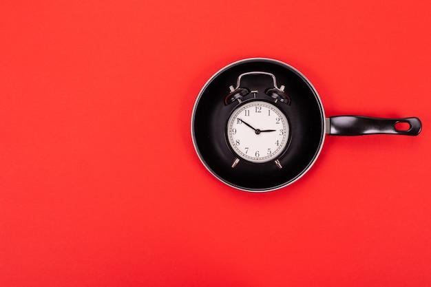 Bovenaanzicht van wekker in pan geïsoleerd op rood Premium Foto
