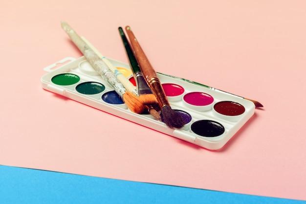 Bovenaanzicht van werkproces lege aquarel papier, aquarel schilderij benodigdheden, penselen Premium Foto